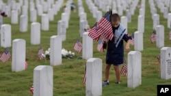 نهادن پرچم آمریکا به مناسبت روز یادبود در گورستان فورت سام هیوستن در سن آنتونیو، تکزاس، ۲۴ مه ۲۰۱۳