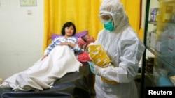 Seorang perawat dengan mengenakan alat pelindung diri untuk mencegah penularan virus corona sedang menggendong bayi yang baru lahir di kamar bersalin di Depok, 13 April 2020. (Foto: Reuters)