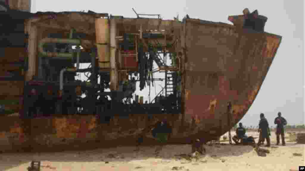 Workers gather in the shade of a derelict ship beached against the coastline of Nigeria.