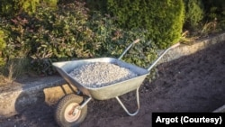 Single wheel garden wheelbarrow loaded with crushed stone prepared for garden path reconstruction in the autumn garden