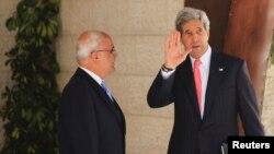Menlu AS John Kerry (kanan) melambaikan tangannya disebelah juru runding Palestina Saeb Erekat sebelum bertemu dengan Presiden Palestina Mahmoud Abbas di Ramallah (23/5).