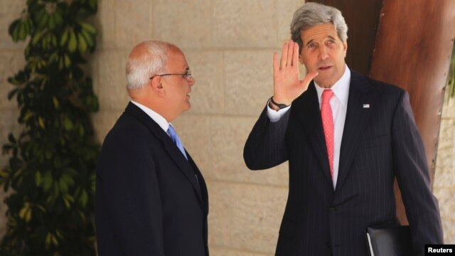 U.S. Secretary of State John Kerry (R) waves as he stands next to Palestinian Chief Negotiator Saeb Erekat before his meeting with Palestinian President Mahmoud Abbas in the West Bank city of Ramallah May 23, 2013.