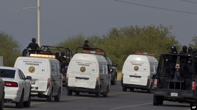 Federal police on vehicles escort the three forensic trucks where bodies were placed after dozens of bodies, some of them mutilated, were found on a highway connecting the northern Mexican metropolis of Monterrey to the U.S. border in the town of San Juan