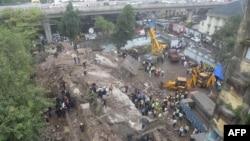 Petugas pemadam kebakaran dan penyelamatan di lokasi gedung roboh di Mumbai (27/9). (AFP/Indranil Mukherjee)