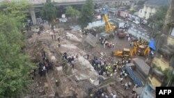 消防员和救援人员在倒塌大楼现场工作。
