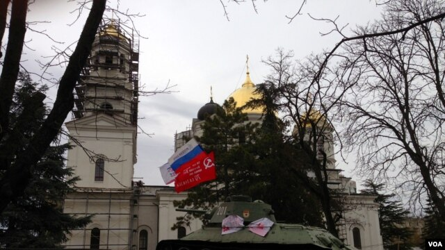 Russian political party flags and a Soviet banner fly at a war memorial in Crimea's capital, Simferopol, Ukraine, March 2, 2014. (Elizabeth Arrott/VOA)