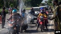 Para petugas menyemprotkan cairan disinfektan kepada para pengendara motor dari Pulau Madura sebelum memasuki Surabaya, Jawa Timur, di tengah perebakan Covid-19. (Foto: AFP)