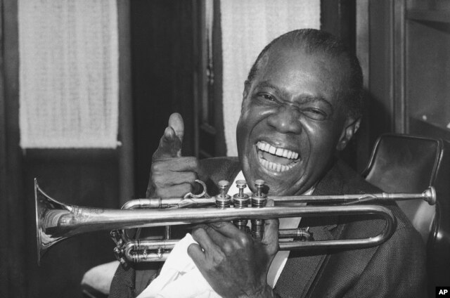 FILE - Jazz trumpeter Louis Armstrong shown in the upstairs den of his Corona, New York home, June 23, 1971.