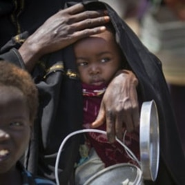 A mother with her child seeking food aid in Mogadishu last month. The United Nations has now declared the end of the famine in Somalia, February 3, 2012