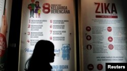 FILE - A woman stands near a poster explaining the Zika virus at the Ministry of Health office in Jakarta, Indonesia, Sept. 2, 2016.