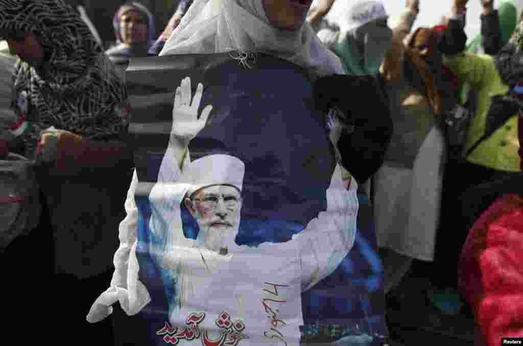 A woman holds a photograph of Tahirul Qadri during a protest in Islamabad, Pakistan, January 14, 2013.