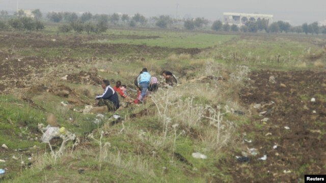 Người dân bỏ nhà chạy trốn sau những vụ ná pháo từ lực lượng trung thành với Tổng thống Bashar al-Assad ở Houla, gần Homs, 3/12/2012.
