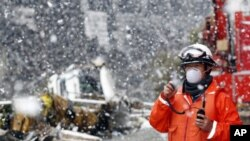 A rescue worker uses a two-way radio transceiver during heavy snowfall at a factory area devastated by an earthquake and tsunami in Sendai, northern Japan, March 16, 2011
