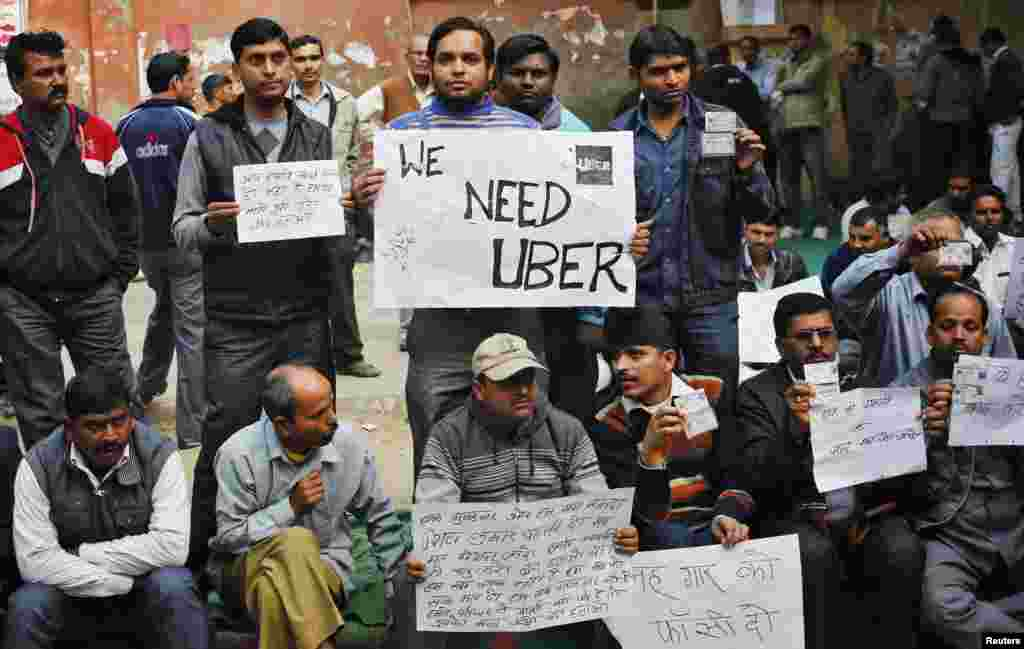 Uber taxi drivers hold placards during a protest against the ban on online taxi services, in New Delhi, India.