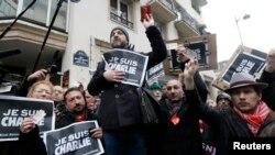 """Các ký giả cầm các tấm bảng với hàng chữ """"Tôi là Charlie"""" và thẻ ký giả, trong một phút mặc niệm các nạn nhân trước tòa báo trào phúng Charlie Hebdo, 8/1/15"""