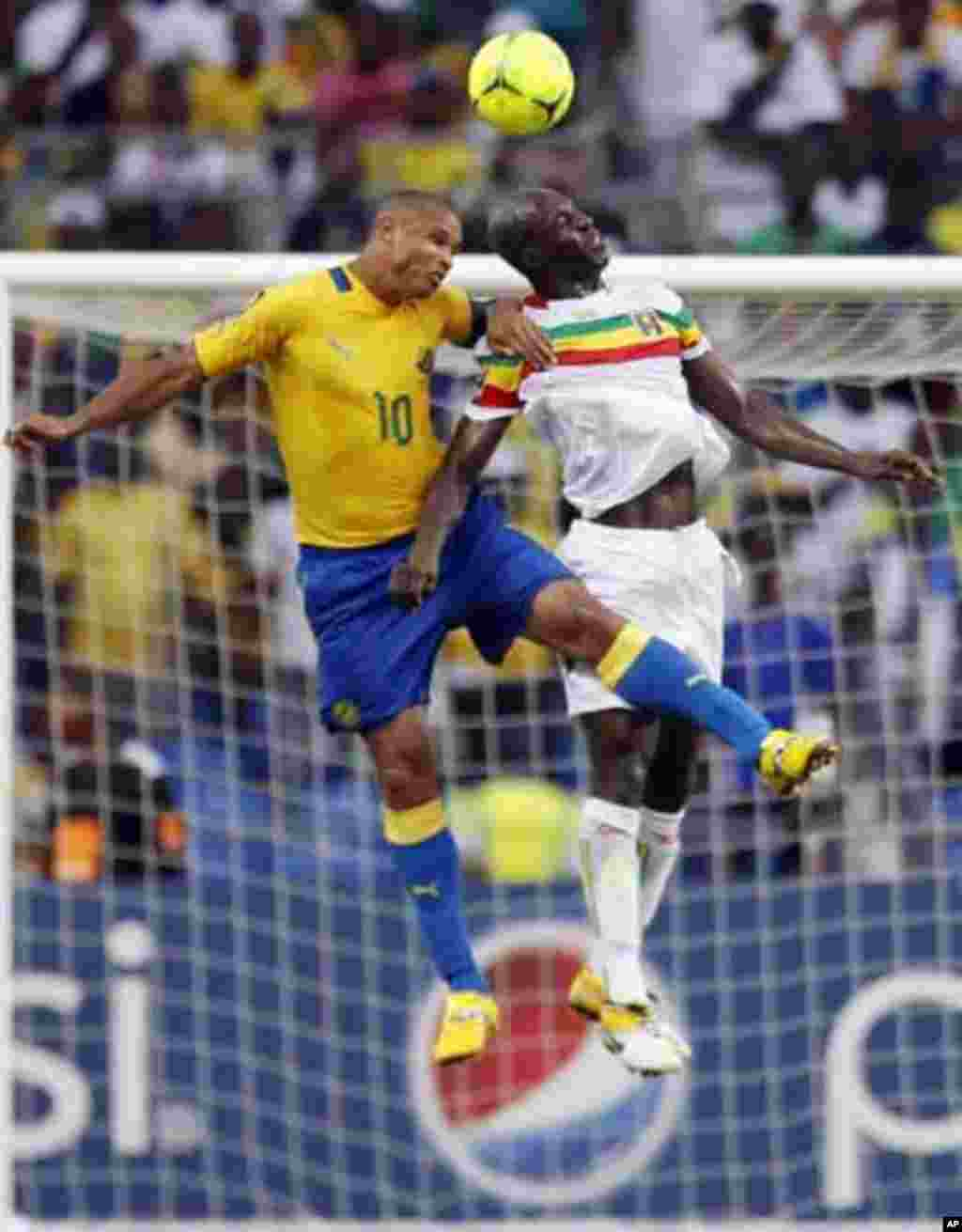 Gabon's captain Daniel Cousin (L) jumps for the ball with Mali's Drissa Diakite during their African Cup of Nations quarter-final soccer match against Mali at the Stade De L'Amitie Stadium in Gabon's capital Libreville February 5, 2012.