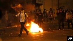 Seorang demonstran menantang barisan Pasukan Nasional Bolivaria dalam aksi protes anti-pemerintah di Caracas, Venezuela (28/2).