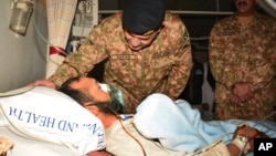 Pakistan's Lt. Gen. Zafar Iqbal Malik enquires about the health of a Kashmiri villager injured by Indian firing, during a hospital visit in Muzaffarabad, Pakistan, Nov. 24, 2016. Pakistan's air force chief has warned arch-rival India against escalating the dispute over Kashmir into full-scale war.