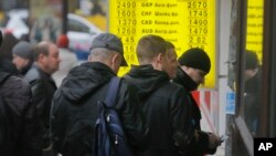 FILE - People stand in line at a currency exchange kiosk in Kyiv, Ukraine.