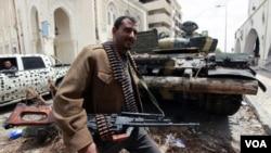 Seorang pemberontak Libya berjalan dekat sebuah tank pasukan Libya yang disita pemberontak di Tripoli, Jumat (22/4).