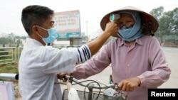 越南一名衛生工作者正在檢測一名農民的體溫(2020年2月12日)。