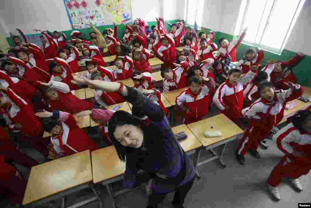 A teacher leads her students doing body exercise during class break in a classroom on a foggy day in Jinan, Shandong province, January 14, 2013. Heavy fog enveloped a large swathe of east and central China, with the city's residents being advised to stay