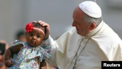 El Papa Francisco bendice a una niña