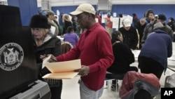 Nhân viên bầu cử giúp đỡ cử tri tại một địa điểm bỏ phiếu ở New York, ngày 6/11/2012.