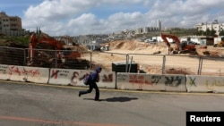 A boy runs past a road under construction in the Arab neighborhood of Beit Safafa in Jerusalem February 28, 2013.