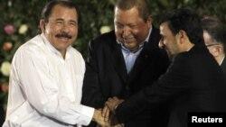 El presidente de Nicaragua, Daniel Ortega, se toma las manos con su homólogo venezolano, Hugo Chávez (centro), y el mandatario iraní, Mahmoud Ahmadinejad (izquierda).