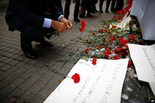 A man leaves carnations at the Saturday explosion site in Istanbul, March 20, 2016.
