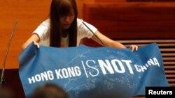 """香港立法会新一届非建制派议员在就职宣誓仪式上展示出用英文写的""""香港不是中国""""的蓝色旗帜(2016年10月12日)"""