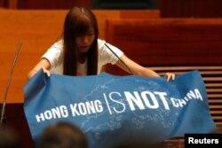 """香港立法会新一届非建制派议员游蕙祯在就职宣誓仪式上展示出用英文写的""""香港不是中国""""的蓝色旗帜(2016年10月12日)"""
