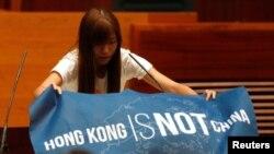 """香港立法會新一屆非建制派議員在就職宣誓儀式上展示出用英文寫的""""香港不是中國""""的藍色旗幟(2016年10月12日)"""