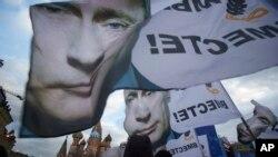Warga di Moskow memberikan dukungan penggabungan Krimea dengan Rusia, dengan membawa spanduk dan potret Presiden Rusia Vladimir Putin (18/3). (AP/Pavel Golovkin)