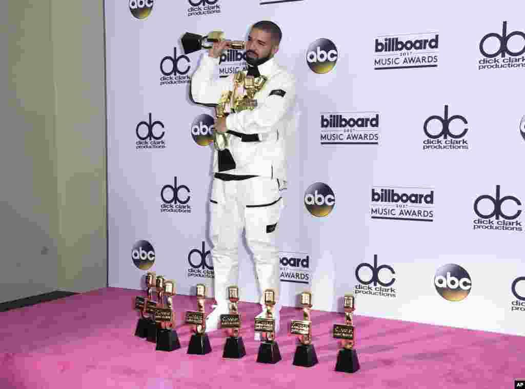 លោក Drake ឈរថតរូបនៅក្នុងបន្ទប់សារព័ត៌មានជាមួយនឹងពានរង្វាន់ចំនួន១៣របស់គាត់នៅក្នុងកម្មវិធី Billboard Music Awards នៅមជ្ឈមណ្ឌល T-Mobile Arena នៅក្នុងក្រុង Las Vegas រដ្ឋ Navada កាលពីថ្ងៃទី២១ ខែឧសភា ឆ្នាំ២០១៧។