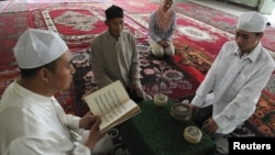 A Muslim man from the Chinese Hui minority reads the Koran as others listen in a sitting room in Aksu, Xinjiang Uighur Autonomous Region, July 27, 2012.