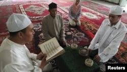 A Muslim man from the Chinese Hui minority reads the Koran as others listen in a sitting room in Aksu, Xinjiang Uighur Autonomous Region, July 27, 2012.