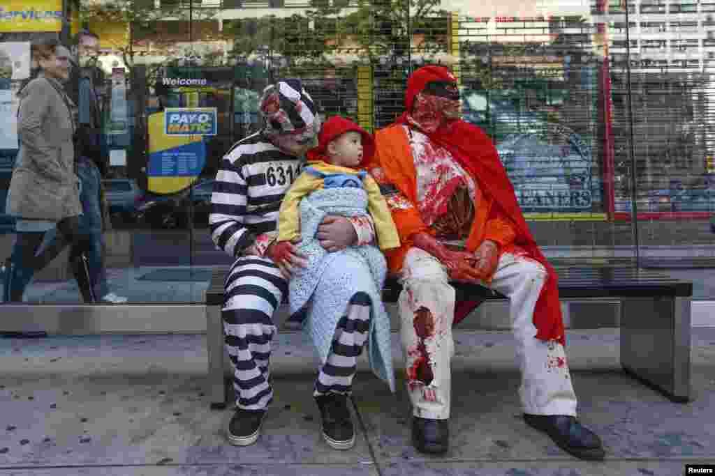 دو مرد با یک پسر خورد سال در شهر نیویارک با لباس های عجیب و چهره های ترسناک در انتظار رسیدن شب و جشن هالووین استند