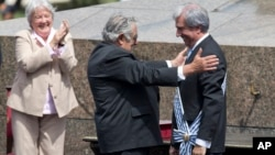 Uruguay's outgoing President Jose Mujica, center, reaches out to new President Tabare Vazquez during Vazquez's inauguration ceremony at Independence Plaza in Montevideo, March 1, 2015.