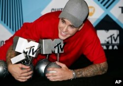 Justin Bieber poses with his awards during a photo call at the 2015 MTV European Music Awards in Milan, Italy, Oct. 25, 2015.