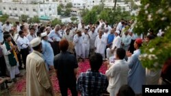 People gather at the grave of Zara Shahid Hussain, a senior politician from the Tehreek-e-Insaf political party headed by cricketer-turned-politician Imran Khan, during her funeral in Karachi, May 19, 2013.