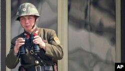 2013年4月4日,在南北双方边界的板门店非军事区,一名朝鲜士兵在观看对方韩国的情况。