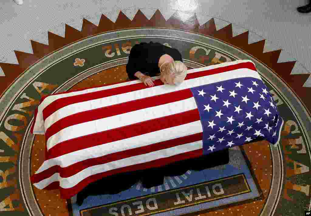 Cindy McCain, wife of the late Sen. John McCain, R-Ariz. lays her head on casket during a memorial service at the Arizona Capitol, Aug. 29, 2018, in Phoenix, Arizona.