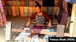 Seorang perempuan Dusun Sasak Sade sedang menenun kain untuk dijual kepada pengunjung (Foto:VOA/ Petrus Riski).