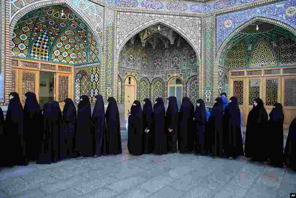Iranian women stand in line at a polling station during the parliamentary and Experts Assembly elections in Qom, 125 kilometers (78 miles) south of the capital Tehran, Iran, Feb. 26, 2016.