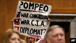 Retired U.S. Army Col. Ann Wright, center, protests the nomination of CIA Director Mike Pompeo, front right, for secretary of state, as he waits to testify before the Senate Foreign Relations Committee during a confirmation hearing on his nomination to be Secretary of State, Thursday, April 12, 2018 on Capitol Hill in Washington.