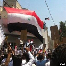 Pendukung Presiden Bashar al-Assad mengibarkan bendera Suriah di halaman Gedung Kedubes AS di Damaskus (11/7).