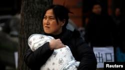 一位妇女抱着裹着严严实实的孩子离开北京一家儿童医院。(资料照)