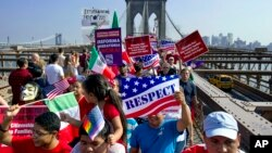 Decenas de inmigrantes cruzan el puente Brooklyn durante la marcha por la dignidad y el respeto hacia los inmigrantes indocumentados en busca de una reforma del sistema de inmigración.
